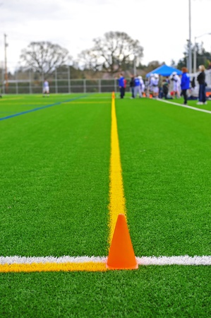 An orange cone marke the corner of the out of bound lines on a turf field with a lacrosse players in the background. photo