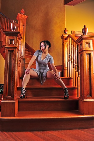 hair tied: A seductive beautiful young Asian woman high heels and a short dress sits on the stairs.