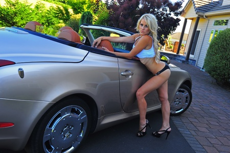 Beautiful blond woman wearing a white tank top over her black bikini and hi heels leans over the passenger door ready to get into this luxury convertible sports car. Stock Photo