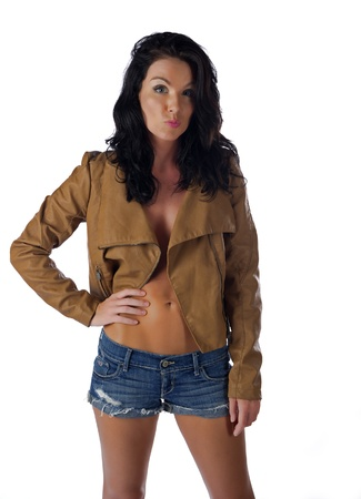 Beautiful brunette in short shorts and a leather coat photo