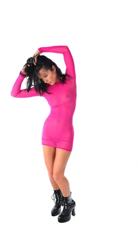 A beautiful brunette in a sheer hot pink dress raises her hands over her head as she stands with an issolated back ground. Banco de Imagens