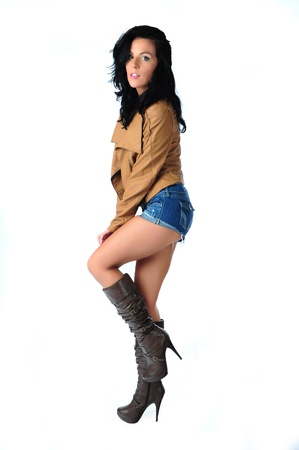 Isolated on a white background, A profile of a sexy brunette wearing a brown leather coat and blue jean cut offs while looking into the camera with a look on her face.