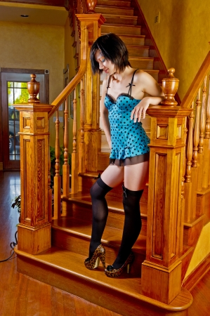 A relaxed beautiful woman rests her arm on the hand rail post of a solid wood stair casing as she pauses and looks down with her other hand on her hip. photo