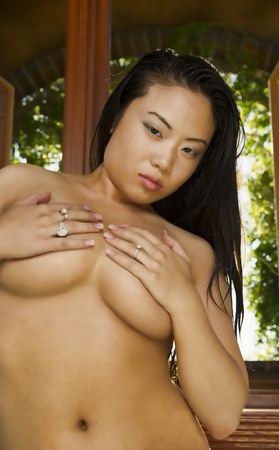 A beautiful sexy Asian woman covers her breast with her hands as she stands in front of a large window.