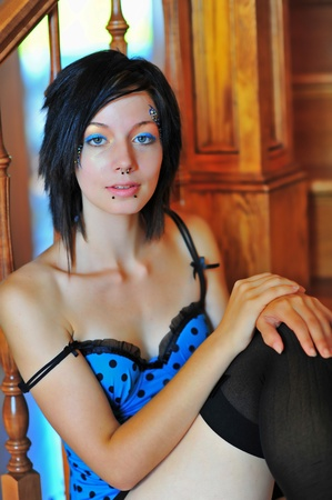 A sensual brunette waits for her mate as the strap of the blue teddy she is wearing slips down on her shoulder.