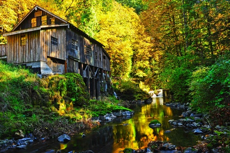 Bright fall autumn surround this old grist mill and reflect in the shadows of the small stream. photo
