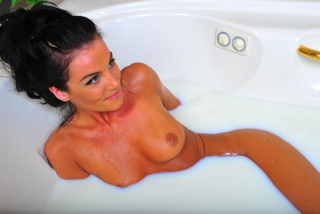 A sexy nude brunette woman relaxes as she soaks in a luxury tub filled with milk.