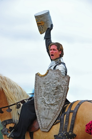 trusty: Saturday August 13, 2011 Washington State Renaissance Fayre held this year in Bonney Lake Washington.  Here the victorious Scottish Knight holds his trusty old shield that has saved him many times and his helmet is held hi above his head as he shouts to t