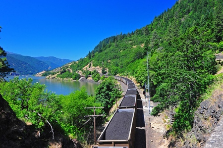 Train cars full of coal are being transported along the rail line through a scenic columbia river gorge. Stock Photo