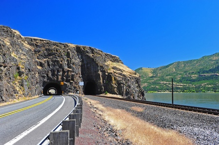 tunnel portals: Railroad tracks and a road emerge from a natural face portal tunnel along the Columbia River Gorge on the Washington state side. Stock Photo