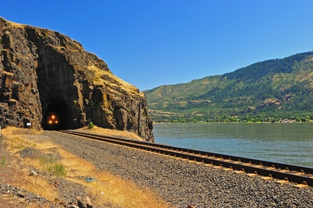 tunnel portals: Lights from a train engine are seen emerging from the natural face portal tunnel along the Columbia River Gorge on the Washington state side. Stock Photo