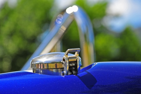 traction: Abstract of a shiny blue restored sports car gas cap and blurred roll bars in the background. Stock Photo