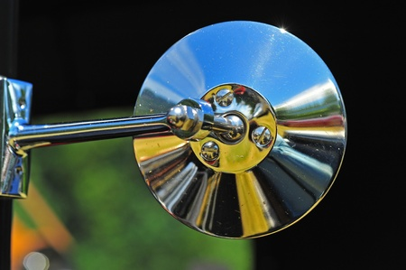 Abstract Retro chrome automotive side view mirror with the automobile not present.  The abstract of the yellows bring you into the center of the photograph. Editorial
