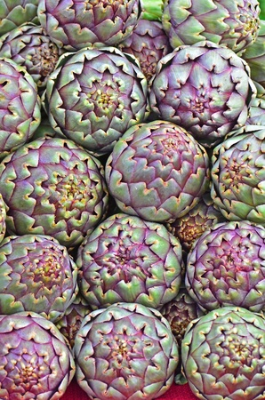 Fresh pile of Italian Artichokes on display at a local farmers market ready for the picking. Stock Photo