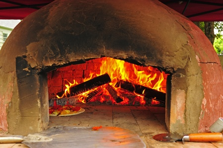 Pizza cooking in the oven next to an open flame of a wood fire with tools of the trade in the fore ground. Stock Photo