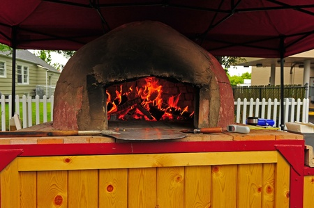 blazes: As a fire blazes in this stone portable pizza oven, the cook is prepared to pull out the cooking pizza when it