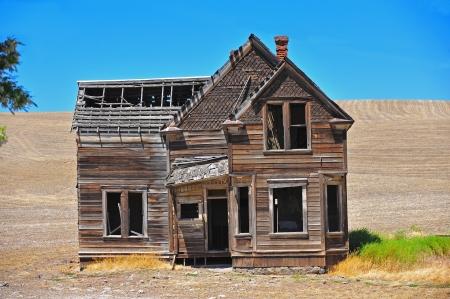 Une vieille maison abandonnée manque le plus de son toit et le terrain autour de lui ramené à la terre avec une petite tache d'herbe verte à côté de lui