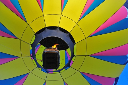 glimpse: A colorful hot air balloon from below the gondola and a glimpse of the flame filling the balloon. Stock Photo