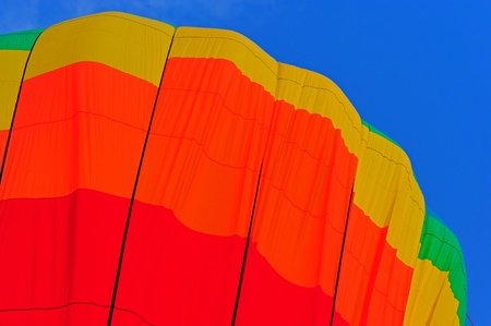 A colorful hot air balloon filling the sky on a clear sunny day. photo