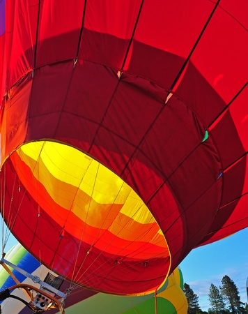 A colorful hot air balloon gets a blast of fire as it is brought to the upright position after inflating it. photo