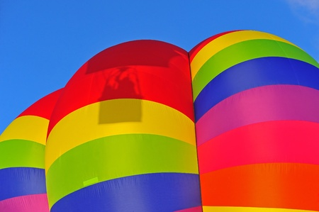 A colorful hot air balloon with the shadow of a passing gondola with passengers passing by. Stock Photo