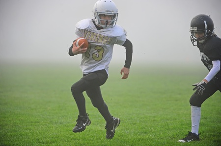 October 22, 2011 American Football Hillsboro Oregon Century High School (Youth Program 5-6th grade) V Forest Grove HS Vikings(Jr High Program).  Viking #13 runs down the field with the ball as a Jag attempts to take down as he comes out of the fog.  Score