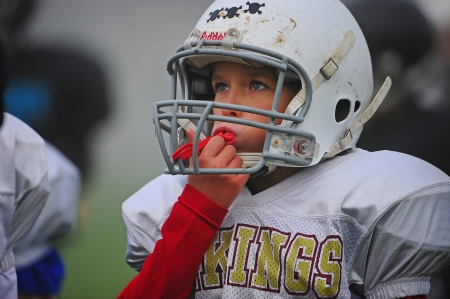 Oct 22, 2011 American Football Hillsboro OR Century High School (Youth Program) V Forest Grove HS Vikings(Jr High Program).  Viking holds onto his mouth guard as he pays attention to the coach during the half time discussion.  Score not kept