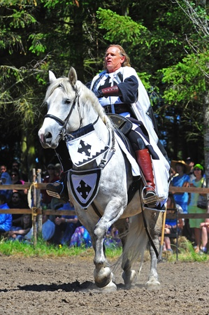 jousting: Saturday July 23, 2011 Canterbury Renaissance Fayre held this year just off Mount Angel Highway in Silverton Oregon.  Here the official for the days jousting competition talks to the spectators as he rides his mount around the arena.