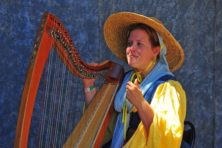 Saturday July 23, 2011 Canterbury Renaissance Fayre held this year just off Mount Angel Highway in Silverton Oregon.  One of the many acts on the various stages, a musician plays the harp to sooth the guest between jousting competitions.