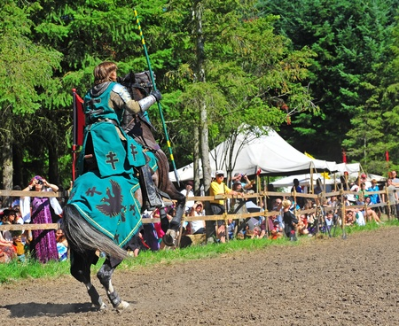 fayre: Saturday July 23, 2011 Canterbury Renaissance Fayre held this year just off Mount Angel Highway in Silverton Oregon.  Here the the green knight mounted on his trusty steed prepares for the ride down the arena and to throw his spear on target.