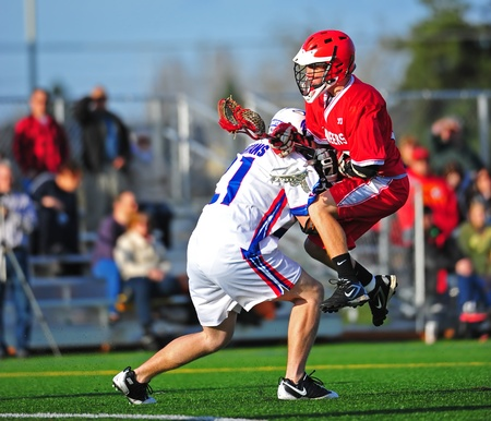 April 08, 2011 OHSLA (Oregon High School Lacrosse Association) Hillsboro's HillHi HS Var V Oregon City Pioneers HS. Spartan #21 runs into and pushes Pioneer #33 back after he takes a shot at the Spartans goal.  Final score 11-3 Oregon City. Stock Photo - 11580960