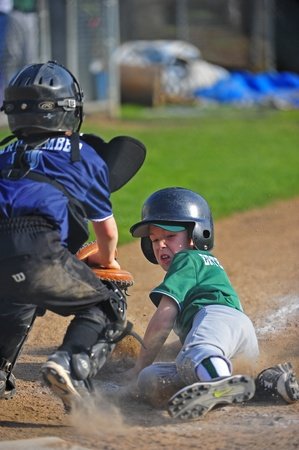 April 23, 2011 Junior Baseball of Oregon Little leauge.  Forest Grove Green V Forest Grove Blue.  Green pitcher slides into home as Blue catcher waits to tag him with the ball for an unsucesfull steal.  Blue team forfeited in 5th of 6 innings.