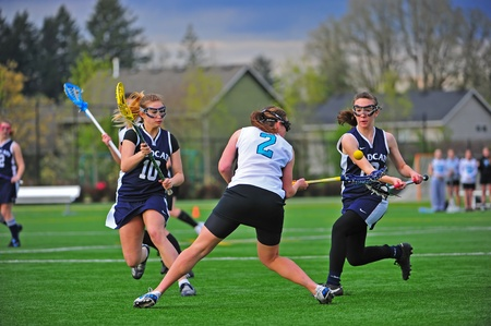 May 05, 2011 OGLA (OR Girls Lacrosse) Hillsboro OR Century HS Jags Var V Wilsonville HS Wildcats. Wildcats double team Century Jag #2 Mareen Dunlop and sucessfully check her knocking the ball out of her stick.  Final score 24-12 Century. Stock Photo - 11593573
