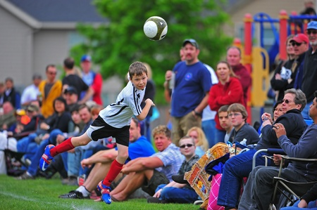 children at play: 05-21-2011 Hillsboro Or parks and rec youth soccer leauge.  FC Portland Shark FIns V West Side Warriors Incas.  FC Shark fin #5 uses his head to keep the ball in play as he heads towards the crowd.  Final Score 6-3 West Side Warrior Incas.