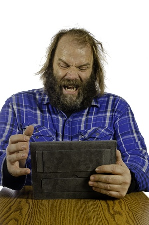 A bearded man wearing a flannel shirt is shares his frustration with this modern technology as he yells uncontrollably and looses his temper while working on a tablet  Stock Photo - 13709950