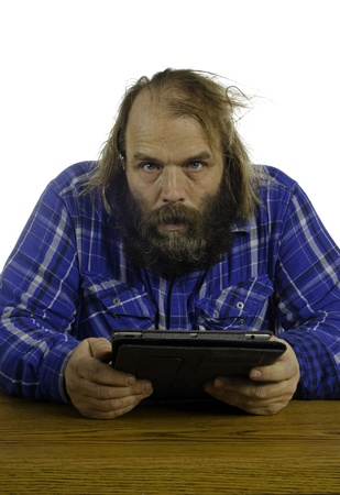 What appears to be a frustrated angry man looks up at you from the tablet he is holding in his hands with a crazed look in his eyes and his hair a mess looking pretty scary