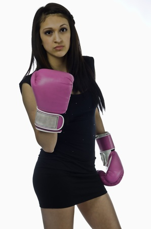 A beautiful young woman in a little black dress holds up a bright pink boxing glove as she looks into the camera with some attitude and ready to fight