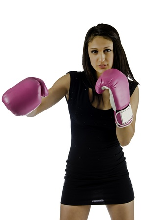 A beautiful young woman in a little black dress and hi heels wearing boxing gloves with her right cross