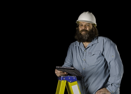 A bearded man in a white hard hat looks at the camera with a slight smile as he holds a tablet in a protective case as he stands on a ladder isolated on a black background  photo
