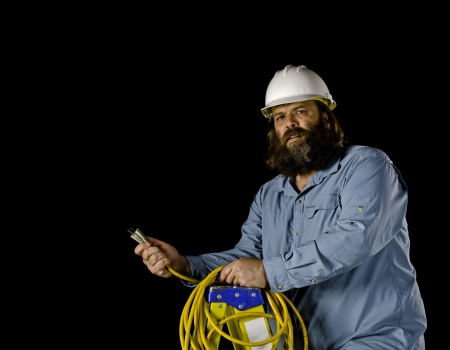 prongs: A bearded man in a white hard hat looks at the camera as though he is confused as he holds an extension cord in his hands with bent prongs as he stands on a ladder isolated on a black background  Stock Photo