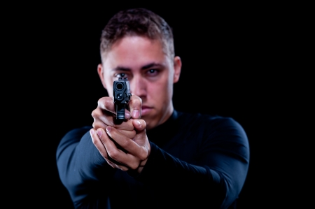 barell: Abstract isolated on a black background, a man dressed in black pointing a hand gun directly at the camera, and as you look just above the barell you can see his eye behind the sights