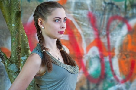 A beautiful young woman leaning against a tree with graffiti wall in the distance  Stock Photo