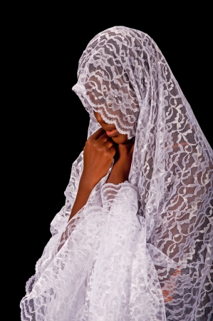 A beautiful young woman wearing a white veil isolated on a black background  Stock Photo - 13707866