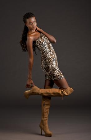 women in boots: Beautiful young black woman grabing her heel