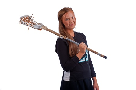 High school girls lacrosse player isolated on a white background and dressed in a black uniform holds her stick over her shoulder as she looks over towards the camera with the free hand on her hip