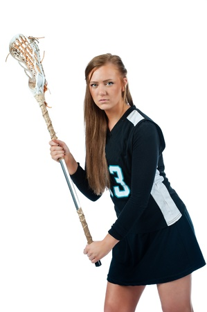 High school girls lacrosse player isolated on a white background and dressed in a black uniform looks over towards the camera as she holds her stick in the ready position to defend her end of the field