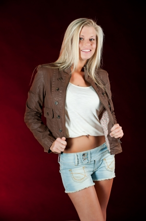 Sexy young blond woman in a brown leather coat with a glow from the setting sun photo