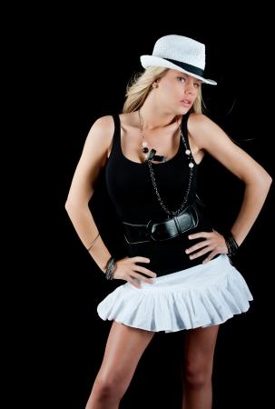 falda corta: Sexy rubia en una falda blanca y sombrero aisladas en negro