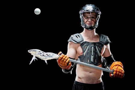 Lacrosse player cathcing ball isolated on black photo