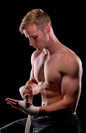 Boxer wraping his wrist on a dark background Stock Photo